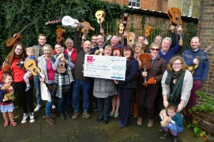 Ver Players ukulele players handing over a cheque for £7,500